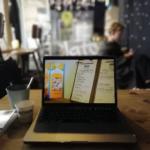 Blick vom Tisch mit Laptop und Kaffeebecher in der AROMA KAFFEEBAR in München