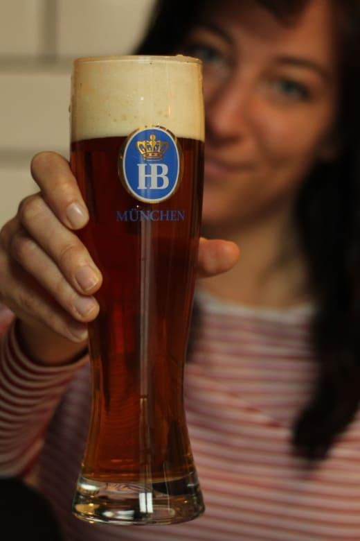 Frau hält Glas mit Münchner Bier