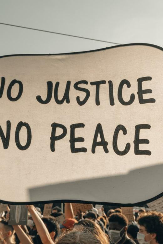 Keine Gerechtigkeit - kein Frieden - Demonstrantin hebt Protestschild hoch